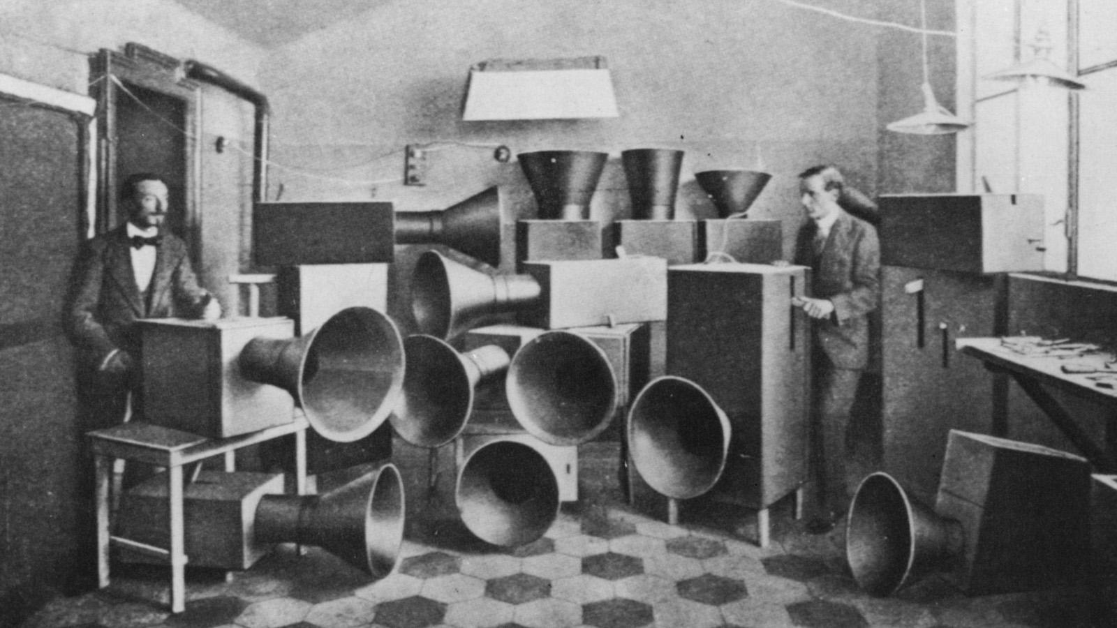 """Luigi Russolo (a sinistra) insieme a un suo assistente, con una serie di """"intonarumori"""", strumenti da lui inventati in grado di generare un rumore modulato in altezza (foto: Hulton Archive/Getty Images)"""